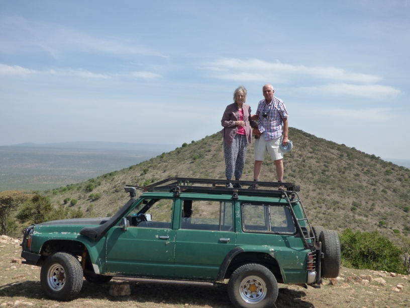 The Coopers survey the terrain from the top of their hosts' four-wheel drive vehicle